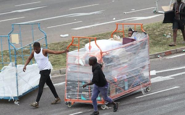 店舗から商品を運び出す人々(13日、ダーバン)=AP