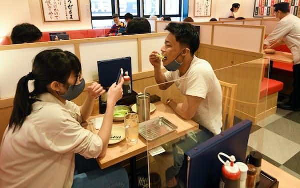 テーブルの間にパーテーションを置き、感染対策を行う串かつ店