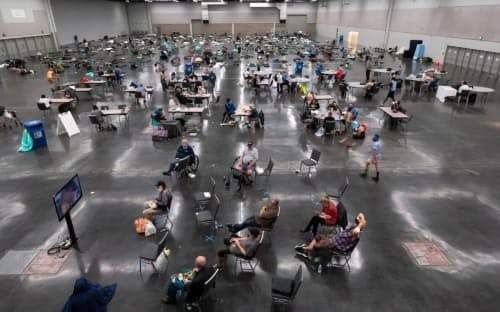 歴史的な熱波に見舞われた6月、市の救援センターで涼む米オレゴン州ポートランドの住民。気候変動がこの暑さを悪化させたことはほぼ間違いない。(PHOTOGRAPH BY NATHAN HOWARD, GETTY IMAGES)