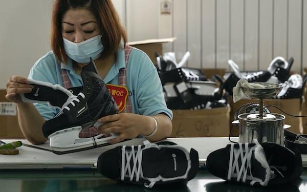 中国河北省の工場でスケート靴をチェックするスタッフ=AP
