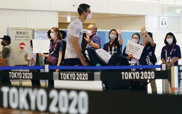 東京五輪の外国人選手をマスク姿で迎える大会関係者(15日)=共同