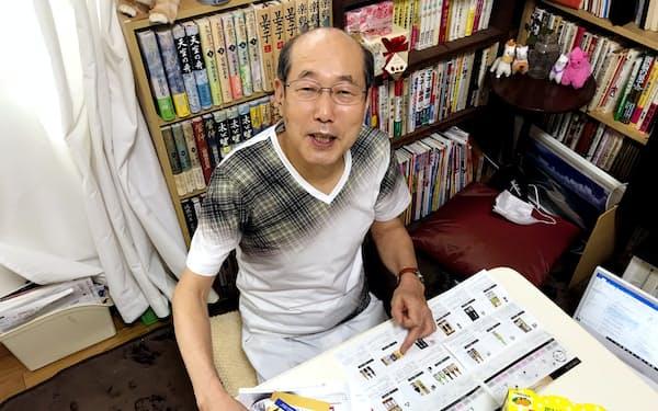 JFLAホールディングスや大和証券グループ本社の優待カタログを見る桐谷さん。手にはミニストップのソフトクリーム無料券も