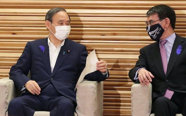 閣議を前にワクチン接種担当の河野規制改革相㊨から渡された資料を手にする菅首相(9日午前、首相官邸)