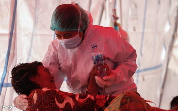 インドネシアの一部病院は新型コロナウイルス感染の急増で病床が足らずテントでの処置を強いられる(15日、ジャカルタ近郊)=ロイター