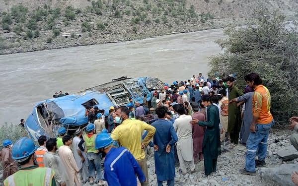 アフガニスタン国境に近いパキスタン北西部カイバル・パクトゥンクワ州で、爆発したバスから乗客らを救出する住民ら(14日)=AP