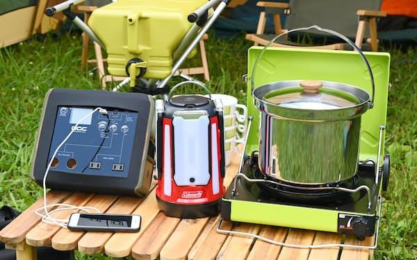 災害時に役立つ(左から)モバイルバッテリー、LEDランタン、カセットガスコンロ。奥にあるのは給水タンクとイス