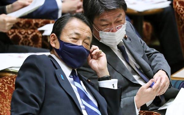 参院決算委で言葉を交わす麻生財務相㊧と茂木外相(4月)