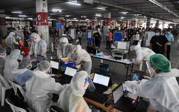 新型コロナウイルス検査に並ぶ人々(15日、バンコク)=ロイター