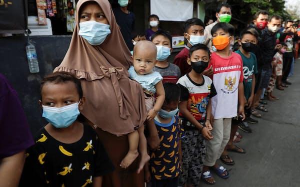 インドネシアのジョコ大統領からの物資の直接支給を待つ住民(16日、ジャカルタ)=ロイター