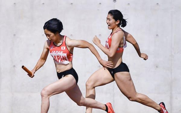 女子400メートルリレー決勝にオープン参加し、第2走者の児玉芽生(右)からバトンを受け走りだす第3走者の斎藤愛美(17日、ヤンマースタジアム長居)=共同