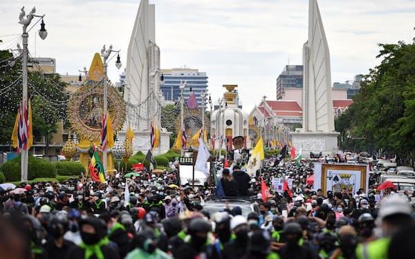 18日、タイ・バンコクの首相府に向けて行進するデモ隊=ロイター