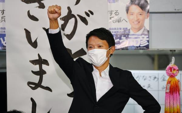 当選が確実となり拳を上げる斎藤元彦氏(18日午後、神戸市中央区)