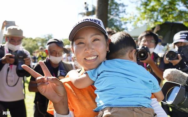 息子を抱き、笑顔でVサインするGMO&サマンサカップ優勝の若林舞衣子=共同
