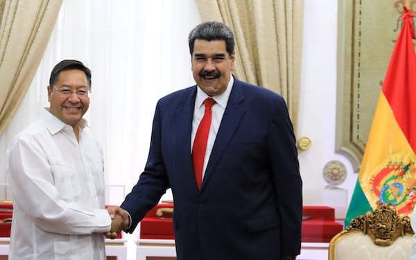 ベネズエラのマドゥロ大統領㊨と握手するボリビアのアルセ大統領(6月、カラカス)=ロイター