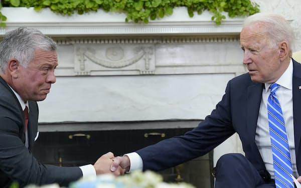 ヨルダンのアブドラ国王(左)と握手するバイデン米大統領=AP