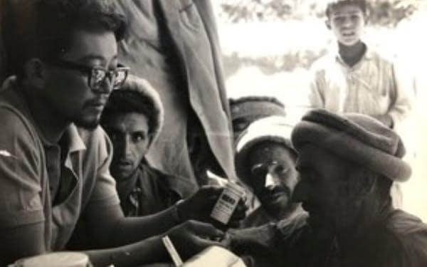 ディラン登山の際、麓の村人を相手に医者のまねごとをする高田直樹(左端、1965年)=同氏提供