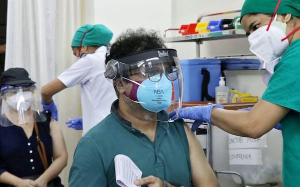 インド企業がライセンス生産する英アストラゼネカのワクチン接種を受ける男性(5月、ムンバイ)=ロイター