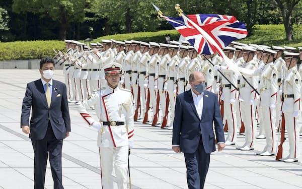 儀仗(ぎじょう)隊の栄誉礼を受けるウォレス英国防相(右)、左は岸防衛相=20日午後、防衛省(代表撮影)