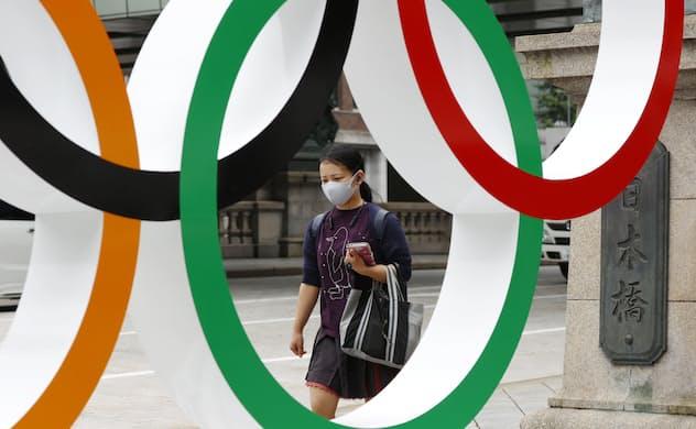 五輪マークのモニュメントの前をマスク姿で歩く人=8日午前、東京都中央区