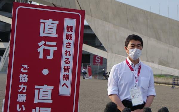 宮城スタジアムに置かれた直行直帰を呼びかける看板前に立つ村井知事(21日、宮城県利府町)