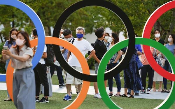 国立競技場近くの五輪マークの前で記念撮影の順番待ちをする人たち(21日)=共同