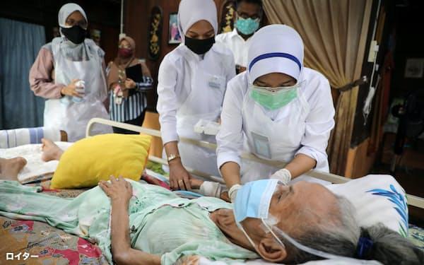 自宅で新型コロナウイルスのワクチン接種を受ける高齢者(17日、クアラルンプール)=ロイター
