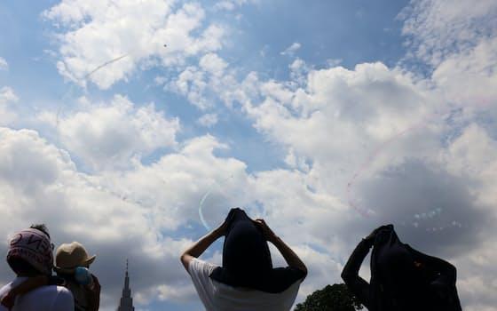 東京五輪の開会式当日を迎え、航空自衛隊のアクロバット飛行チーム「ブルーインパルス」が、国立競技場の上空に五輪マークを描いた(23日、東京都新宿区)