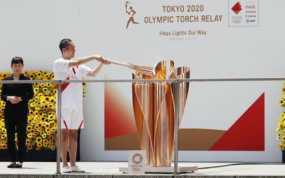 東京五輪の聖火リレーは都内の最終地点となった都庁で到着式が行われた。最終ランナーを務める歌舞伎俳優、中村勘九郎さんが聖火皿に点火した。聖火は夜、開会式が行われる国立競技場の聖火台へ届けられる(23日、東京都新宿区)