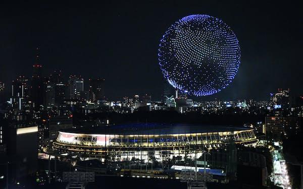 ドローンで国立競技場の上空に描かれた地球(23日午後、東京都内)
