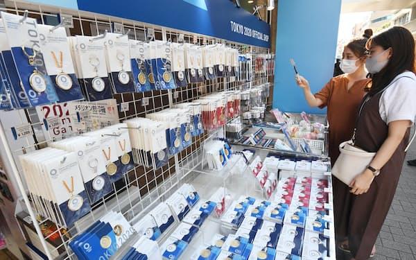 東京2020オフィシャルショップ上野御徒町店で、キーホルダーやメダルの公式グッズを買い求める客(24日、東京都台東区)