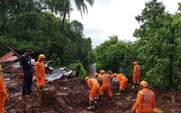 豪雨による地滑りの現場で被災者を捜索する救助隊員ら(インド西部マハラシュトラ州、25日)=ロイター