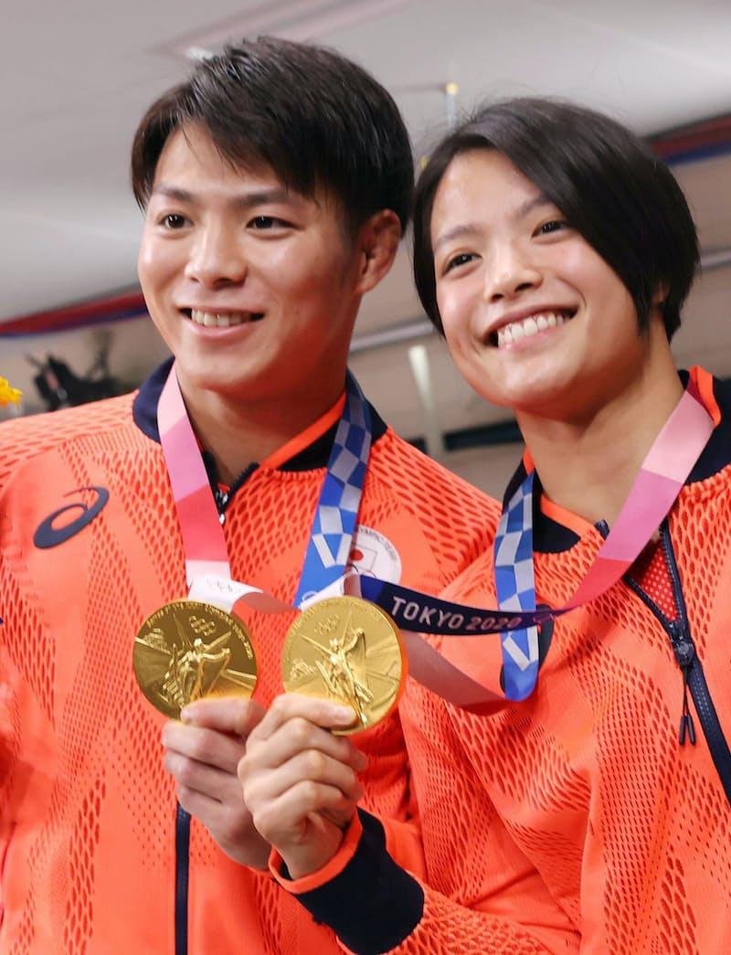 きょうだいで同日に獲得した金メダル手に笑顔を見せる阿部一二三選手㊧と詩選手(25日、東京都千代田区)