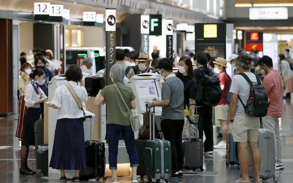 4連休の初日、航空便の搭乗手続きをする利用客(22日午前、羽田空港)=共同