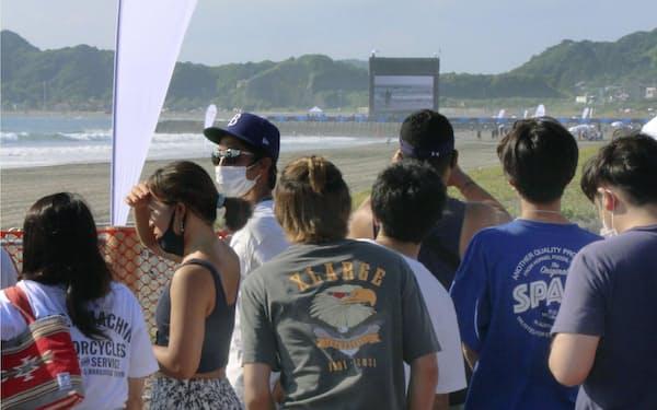 無観客開催のサーフィンをフェンス越しに見学する人たち(25日午前、千葉県一宮町)=共同