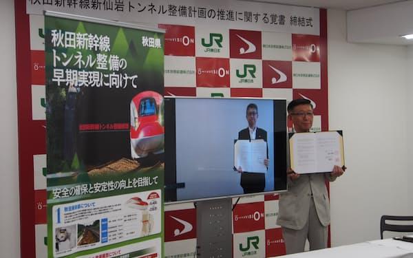 秋田県の佐竹知事㊨とJR東日本の幹部がオンラインで覚書を締結した(26日)