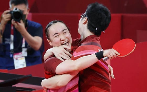 混合ダブルスで中国組を破って金メダルを獲得し、抱き合って喜ぶ伊藤(左)と水谷
