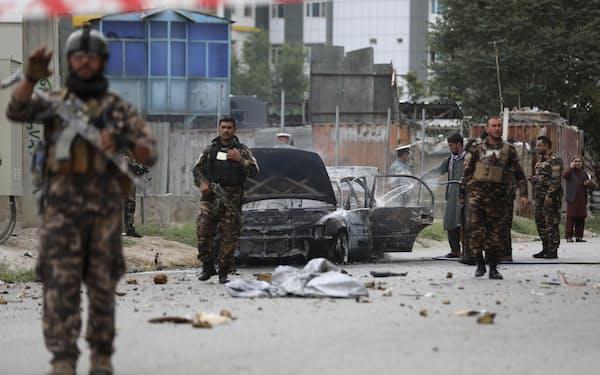 アフガニスタンの首都カブールで、ロケット弾攻撃を受けた車両を調べる治安部隊員ら(20日)=AP