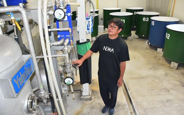 脇坂さんは「焼酎と日本酒の二刀流でいく」と話す(左が蒸留機、右奥が貯蔵タンク)