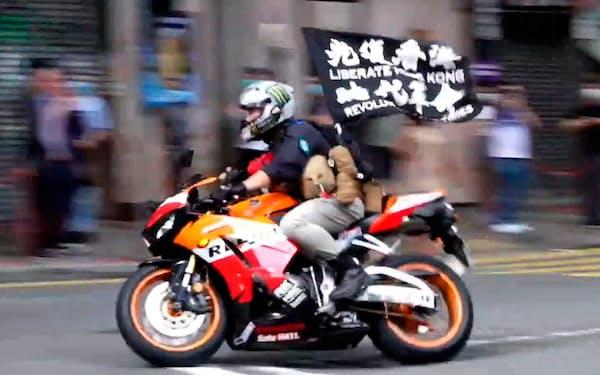 唐英傑被告は「光復香港」の旗を掲げたバイクで警官をはねた(2020年7月)=AP