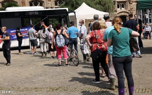 ドイツで新型コロナウイルスのワクチンを接種するため長い列を作る人々=ロイター