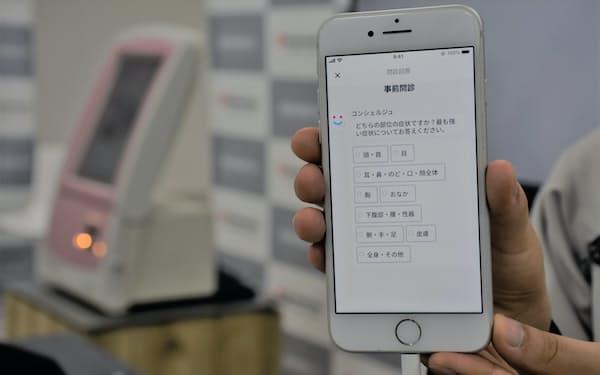 アプリが症状の部位や痛みの種類などの選択肢を示してくれるため、患者は簡単に問診に答えることができる(27日、京都市)