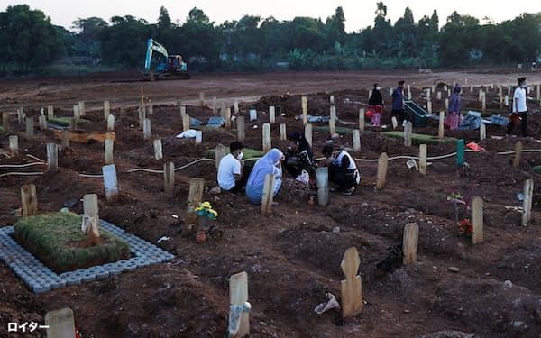 新型コロナウイルスによる死者が埋葬された墓地(27日、ジャカルタ)=ロイター