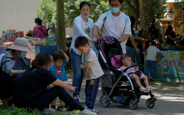 People wearing face masks bring their children tour a public park during the International Children's Day in Beijing, Tuesday, June 1, 2021. China's leaders  have announced it would let all couples have three children instead of two, hoping to counter the rapid aging of Chinese society. (AP Photo/Andy Wong)