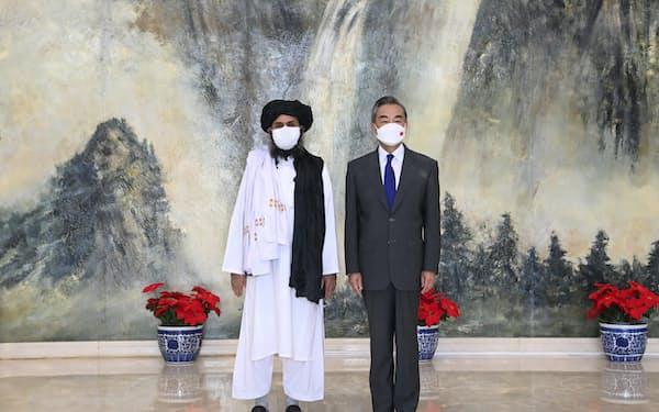 中国の王毅外相㊨と会談するタリバン幹部のバラダル師(28日、天津)=AP