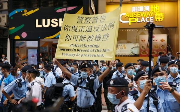 7月1日、毎年恒例の香港返還記念日の反政府集会を阻止するため、デモ行進が禁止されたことを告知する警官隊=ロイター