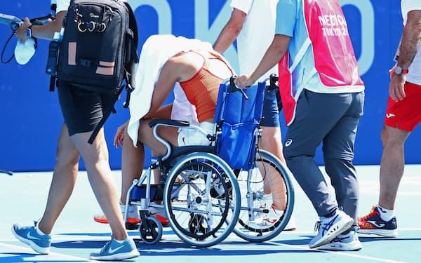 試合中に熱中症になったバドーサは準々決勝を棄権、車いすで会場を引き揚げた=ロイター