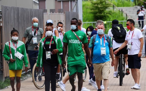 選手村でマスクを着けて歩く関係者ら(29日)=ロイター