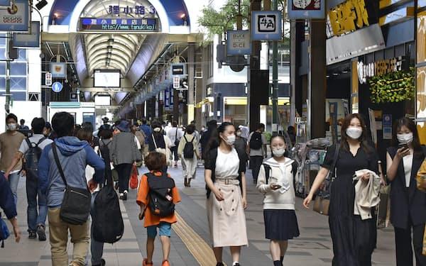 札幌市中心部の商店街をマスク姿で歩く人々=共同