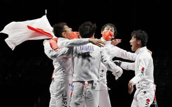 男子エペ団体で優勝を果たし、抱き合って喜ぶ(左から)見延和靖、山田優、宇山賢、加納虹輝の日本チーム=共同