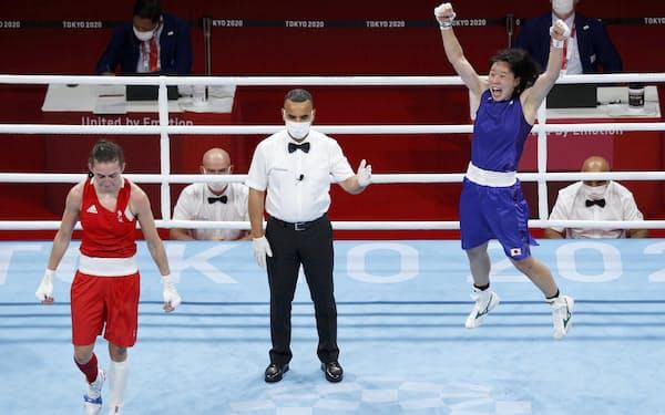 女子フェザー級準決勝で英国選手(左)を破り、決勝進出を決め跳び上がって喜ぶ入江聖奈。銀メダル以上が確定した=共同